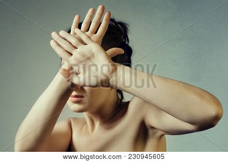 Concept Of Fear, Shame, Domestic Violence. Woman Covers Her Face By Hands On Light Background.