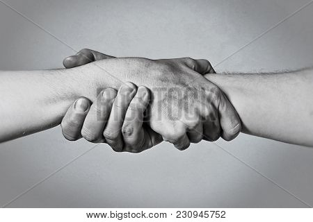Concept Of Salvation. Image Of The Hands Of Two People At The Time Of Rescue (help). Black And White