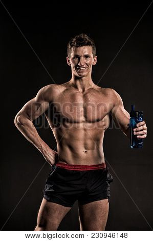 Sportsman With Drinking Water, Fit Torso, Body. Man Athlete Smile With Sport Bottle On Dark Backgrou