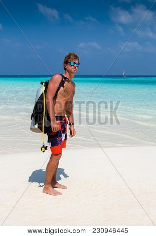 Attractive Male Scuba Diver Standing On A Tropical Beach