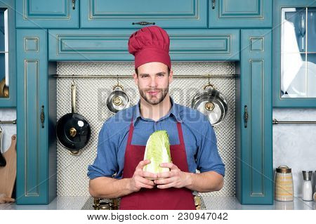 Cook Man Hold Chinese Cabbage In Kitchen. Chef In Red Hat, Apron With Vegetable. Vegetarian, Health,