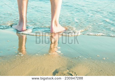 Young Caucasian Man Male Standing Barefooted On Beach Sand By Turquoise Sea. Waves Washing His Feet.