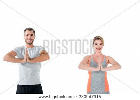 Smiling Couple In Sportswear Practicing Yoga Isolated On White