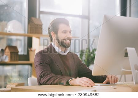 Handsome Architect Working With Computer In Office With Backlit