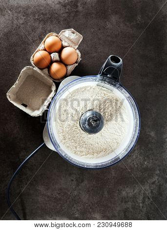 Prepare The Dough From The Eggs  In Food Processor On Grey Stone Table