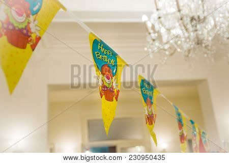 Colorful Party Flags With Clowns And Text Happy Birthday, Hanging On The Rope. Close Up.
