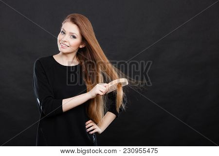Healthy Look Concept. Girl Combing Brushing Her Hair By Using Wooden Comb. Young Woman Taking Care O