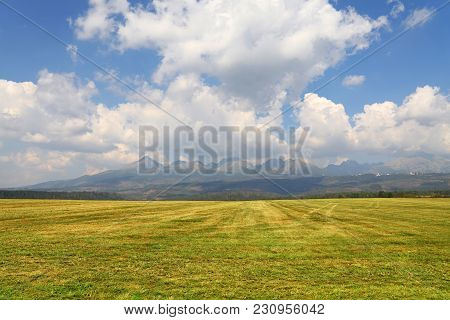 Beautiful Tranquil Rural Scene Of Landscape Stubble Green Field, Mountains Range And Cloudy Blue Sky