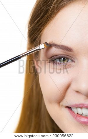 Young Woman Getting Her Eyebrow Make Up Done By Professional Visage Artist. Person Using Brush To Pa