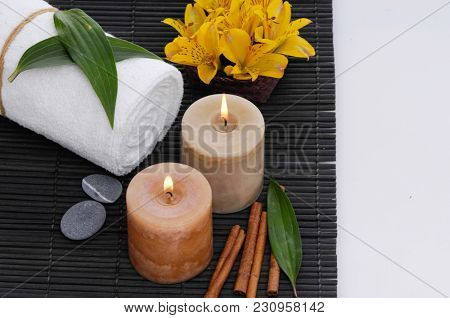 Spa setting with candle, towel ,orchidin bowl, cinnamon on mat