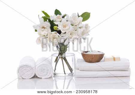 Spa concept with rolled towel, salt in bowl, soap, with gardenia in glass