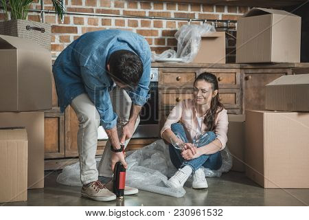 Young Couple With Bottle Of Wine Celebrating Relocation In New House