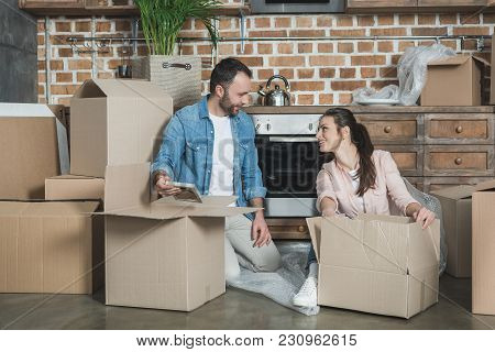 Happy Young Couple Smiling Each Other While Unpacking Boxes In New Apartment