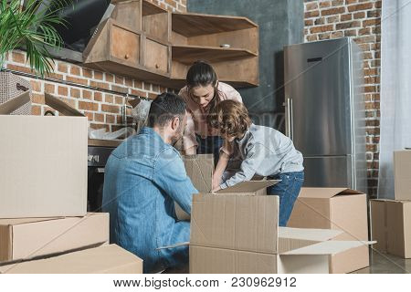 Family With One Child Unpacking Cardboard Boxes In New Apartment