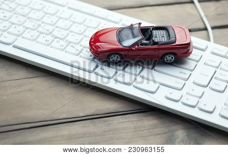 Red Car On The Keyboard On Wooden Table