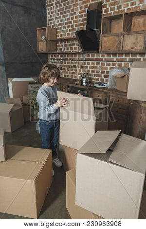 Adorable Little Boy Unpacking Cardboard Boxes In New Apartment