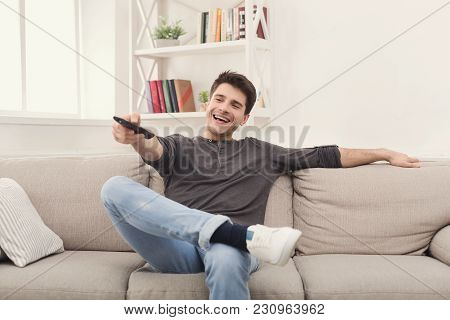 Young Happy Man Watching Tv On The Couch Pointing With Remote Controller On Tv-set, Copy Space