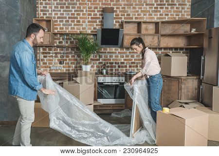 View Of Young Couple Packing Picture During Relocation
