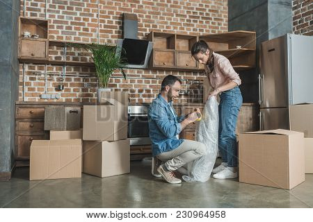 Full Length View Of Young Couple Packing Picture During Relocation