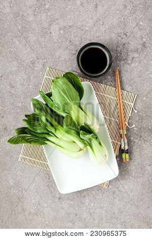 Fresh Not Cooked Bok Choy And Soy Sauce On Grey Table. Chinese Chopsticks. Asian Cuisines Ingredient