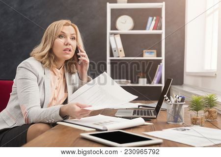 Serious Businesswoman Talking By Phone With Papers, Sitting At Modern Office Workplace, Business Con