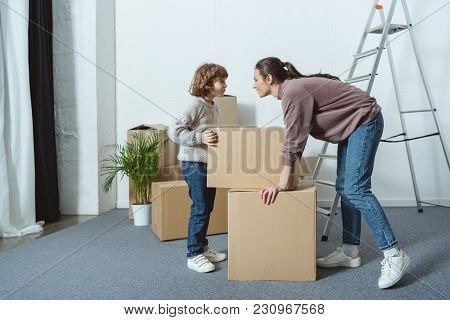 Happy Mother And Son Looking At Each Other While Packing Boxes During Relocation