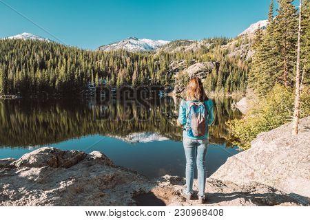 Woman tourist near Bear Lake at autumn in Rocky Mountain National Park. Colorado, USA.