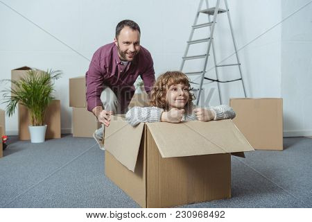 Happy Father And Son In Cardboard Box Having Fun Together While Relocating
