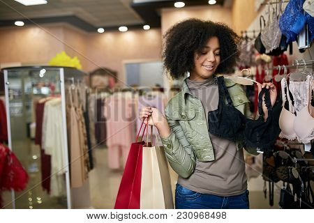 Young Attractive African American Woman Choosing Pretty Bra In Lingerie Store. Black Mixed Race Girl