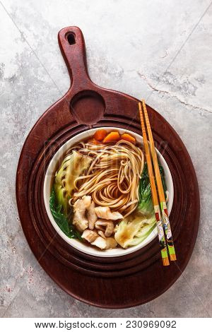 Asian Noodles In Broth With White Fish, Bok Choy  In Wooden Tray On Grey Background