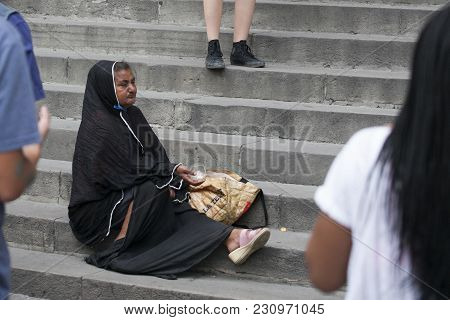 Barcelona, Spain - July 26, 2016: The Poor Beggar Woman Sits On The Pavement.