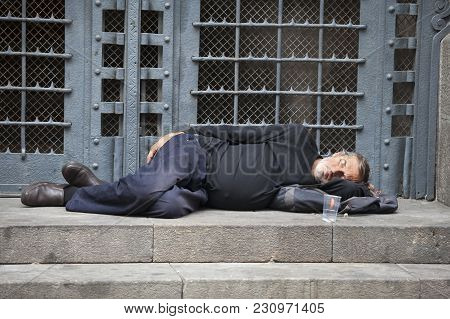 Barcelona, Spain - July 31, 2016: Homeless Person Is Sleeping On A Bench In A Sunny Day In A Steps O
