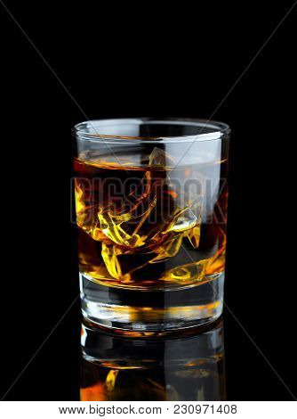Whiskey In The Glass With Ice On Black Background With Reflection. Close Up View.