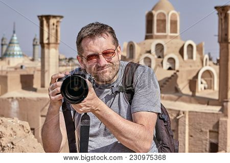 The Tourist Has Lifted The Camera To The Level Of The Face And Is Looking For An Object For Photogra
