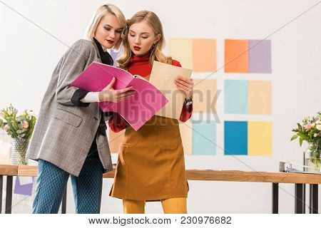 Fashionable Magazine Editors Working With Documents In Modern Office With Color Palette On Wall