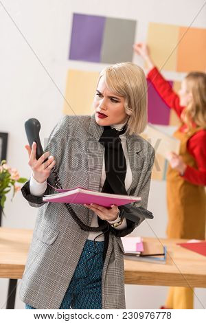 Confused Magazine Editor Looking At Phone While Her Colleague Working With Color Palette Behind