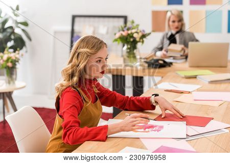 Beautiful Magazine Editor Working With Sketches In Modern Office, Colleague With Laptop Behind