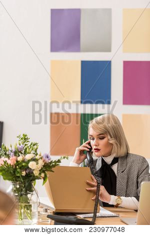 Attractive Fashion Magazine Editor Working With Documents And Talking On Phone