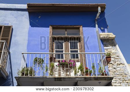 Elements Of The Facade Of The Old House Close-up: Wooden Window And Balcony, Decorated With Flowers