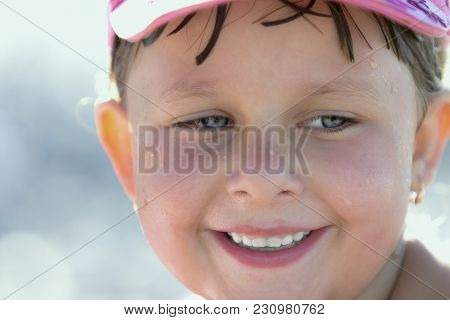 Portrait Of A Beautiful Liitle Girl Close-up Bathed With Wet Hair Wet In A Cap