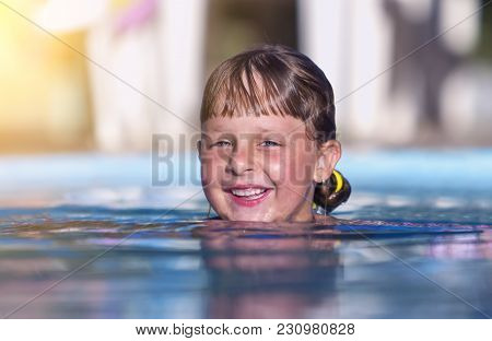The Head Of A Small Smiling Swiming Girl With A Wet Hair Above The Surface Of The Water. Close-up