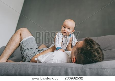 Young Father Lying On Sofa And Playing With Beautiful Infant Child