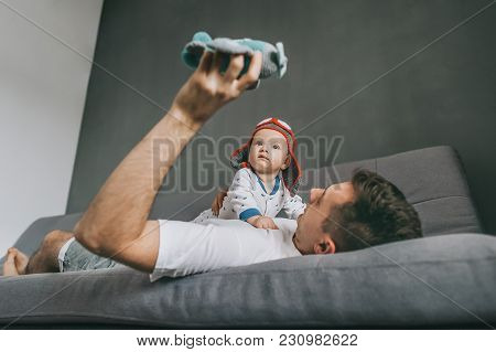 Father Holding Toy Plane While Lying On Sofa And Playing With Adorable Infant Child Wearing Knitted