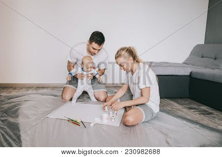 Happy Young Family With Beautiful Little Infant Child Painting Together On Floor At Home