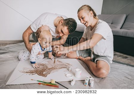 Beautiful Happy Young Family With Cute Little Infant Child Painting Together On Floor At Home