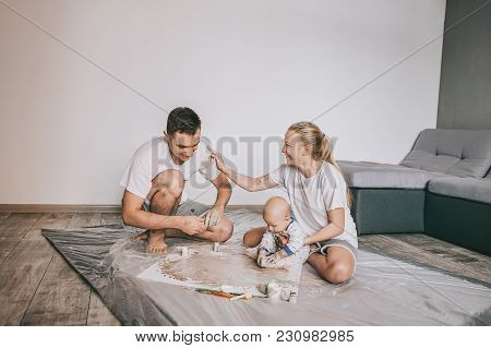 Beautiful Happy Young Family With Adorable Infant Child Painting Together At Home