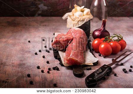 Pork Tenderloin And Other Ingredients On Vintage Wooden Board