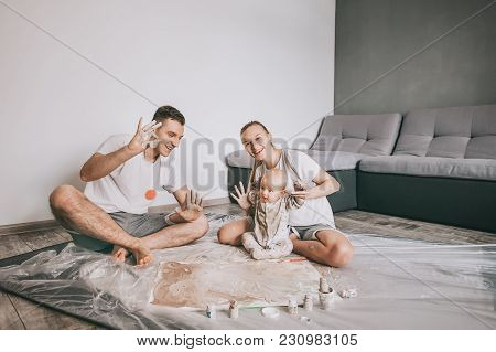 Happy Young Family With Adorable Infant Child Painting Together On Floor