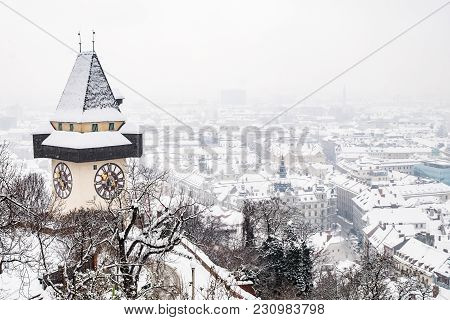 Snow Covered Uhrturm Clocktower Landmark On Hill Schlossberg With Aerial View To City Graz In Winter