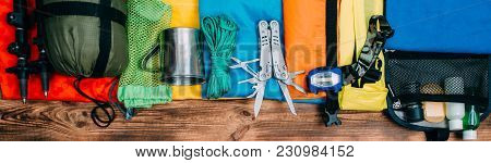 Top View Of Equipment For Hiking And Travel On Wooden Background . Items Include Trekking Pole, Mult